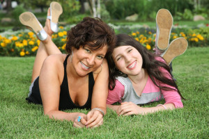 mother and daughter lie on the grass and smile
